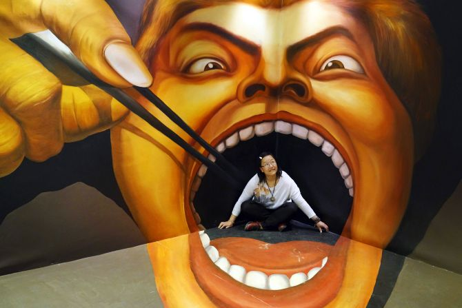 A woman poses for a photograph in front of a 3D painting at an exhibition in Guiyan