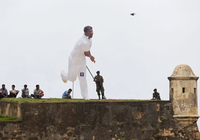 Spectators and soldiers, from behind a cut-out of Sri Lanka's Muttiah Muralitharan, watch cricket match between Sri Lanka and India in Galle