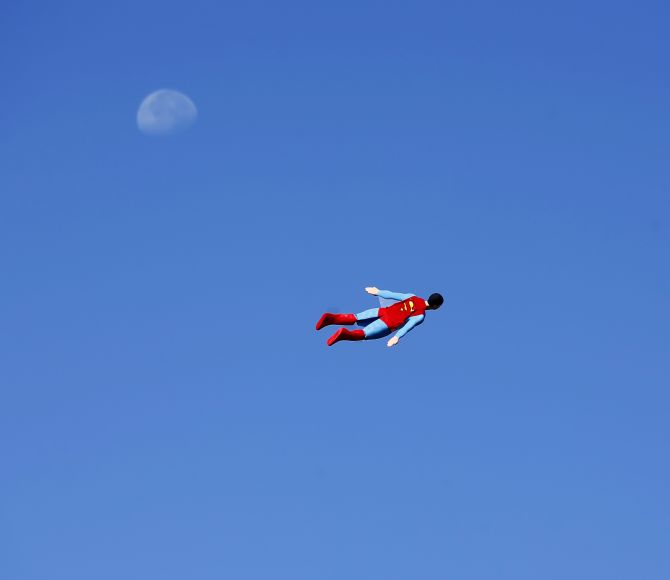 A radio-controlled Superman plane, flown by designer Otto Dieffenbach, passes the moon during a test flight in San Diego