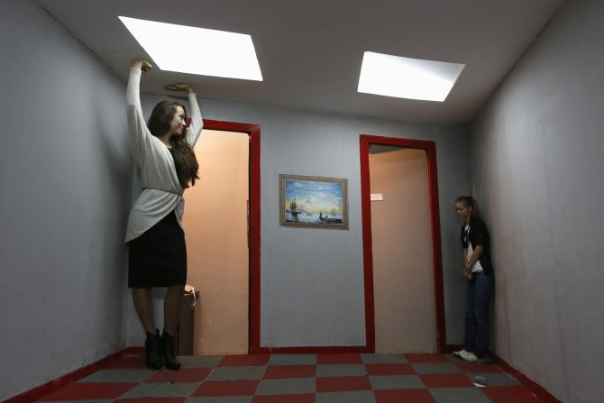 Visitors look at each other in an Ames room at a private exhibition of optical Illusions in St.Petersburg