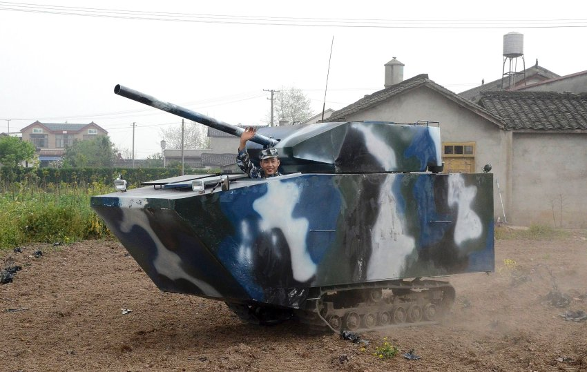 Jian waves in his home-made replica of a tank during a trial run, at a village in Mianzhu