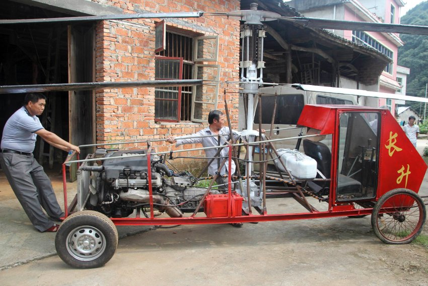 "Villagers help Jiang Changgen move his home-made ""helicopter"" out from a garage before he tries to fly it in Dexing, Jiangxi province"