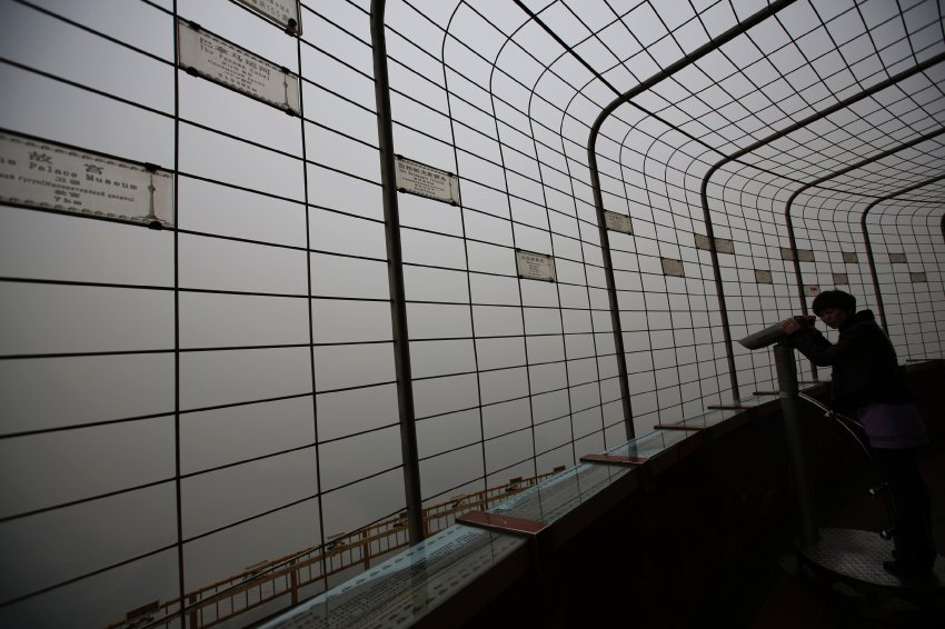 A visitor is silhouetted at an observatory tower during a polluted day in Beijing