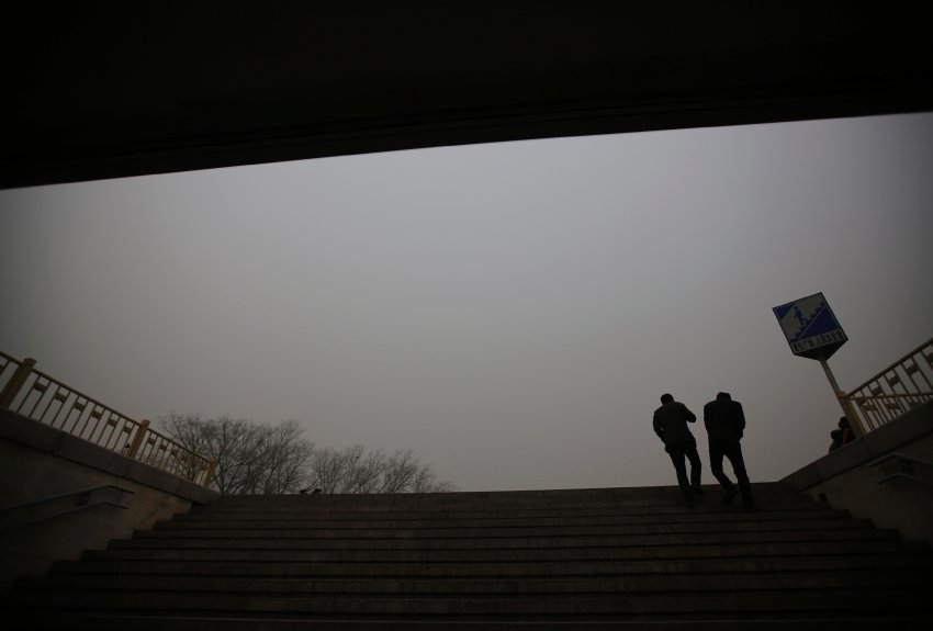 Pedestrians are silhouetted against a hazy sky as they climb a stairs of an underground passage during a polluted day nearby Tiananmen Square in Beijing