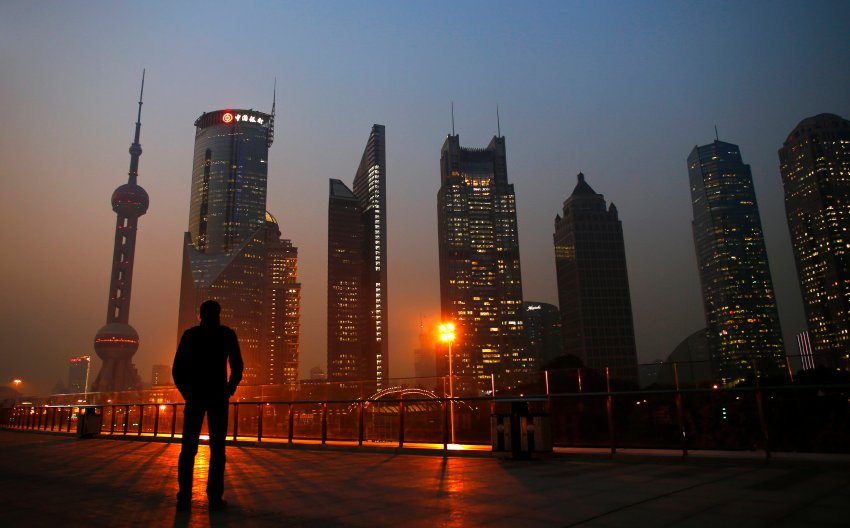 File photo of a man looking at the Pudong financial district of Shanghai