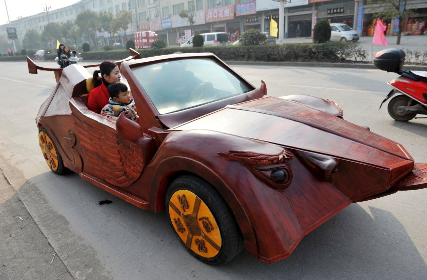 Yu Jietao, 26-year-old wood carver, drives his homemade wooden car along a street with his family, in Guangfeng county of Shangrao