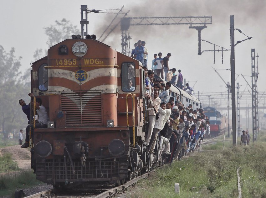 Passengers travel on an overcrowded train at Loni town in Uttar Pradesh