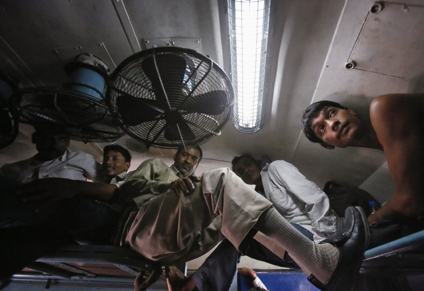 Passengers sit inside a crowded stationary train at a railway station in New Delhi
