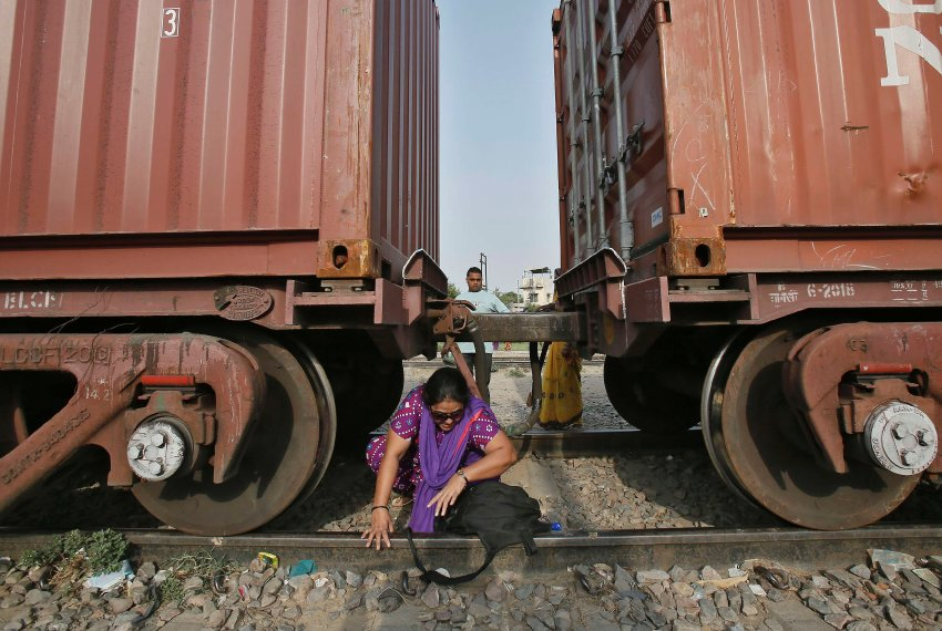 A woman crosses under the carriages of a parked goods train at Loni town in Uttar Pradesh
