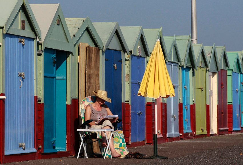 A woman reads as she sits outside a beach hut in Brighton, southern England