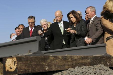 File photo of California Governor Jerry Brown and his wife, Anne Gust, preparing to sign a railroad rail during a ceremony for the California High Speed Rail in Fresno, California