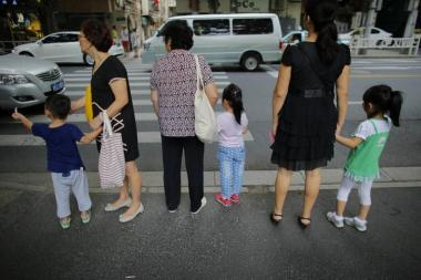 Women hold childrens' hands as they wait to cross a street after school in downtown Shanghai
