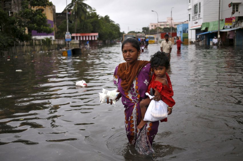 A woman carries her child and milk packets as she wades through a flooded street in Chennai
